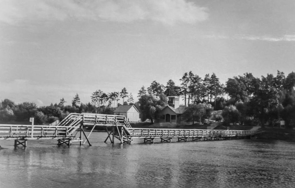 """Деревянный мост в """"Соловьях"""", на месте нынешнего подвесного. У моста – здание спасательной станции (сгорело в 2000-х). Фото 1960-х гг."""